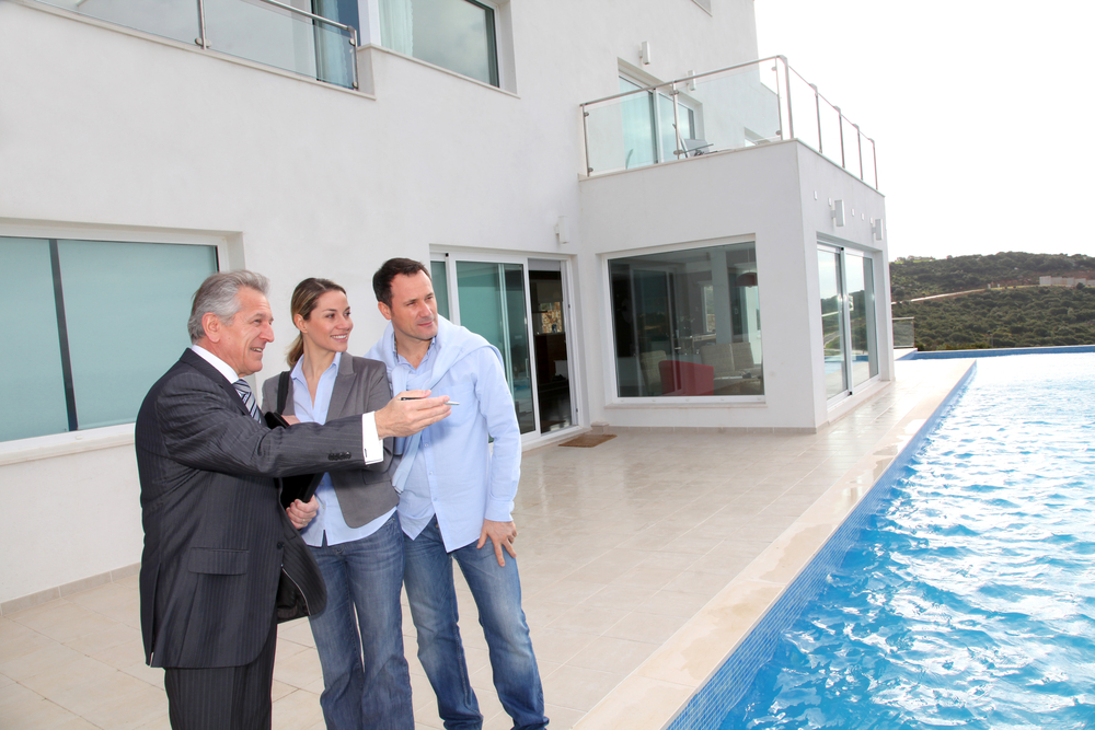Couple visiting luxury villa with real-estate agent