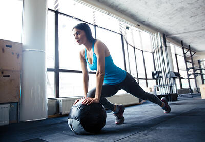 Young woman doing exercise with fit ball at gym